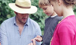 Tobias Miltenberger gibt einem Kind eine Biene auf den Finger